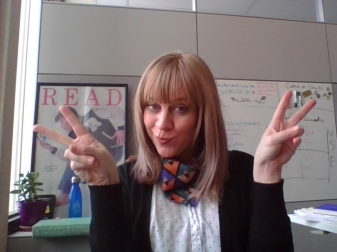 An image of Lindsay Cronk, a white lady doing double peace signs in her office.